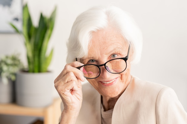 Zeitgenössische elegante weißhaarige frau, die sie durch brillen beim aufstellen betrachtet