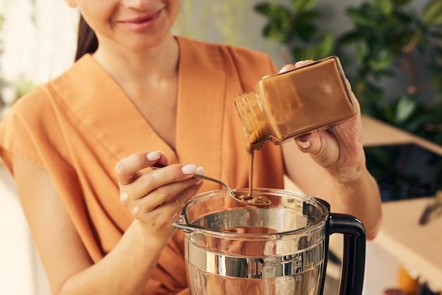 Zeitgenössische frau gießt karamell in mixer mit zutaten