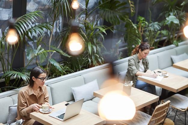 Zeitgenössische frauen, die sich bei cafe terrace entspannen