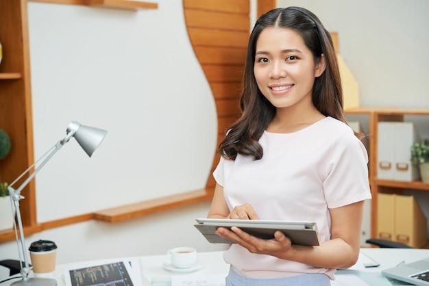 Zeitgenössische geschäftsfrau mit tablette lächelnd an der kamera