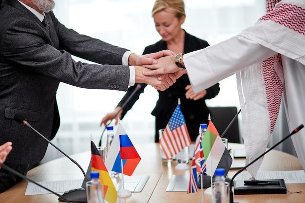 Zeitgenössische interkulturelle delegierte, die sich nach einer erfolgreichen pressekonferenz mit mikrofonen im sitzungssaalbüro die hand schütteln. kaukasische und arabische führungskräfte unterzeichneten ein bilaterales abkommen