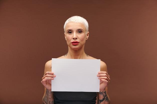 Zeitgenössische junge blonde geschäftsfrau mit tätowierungen auf den armen, die leeres papier mit kopienraum für ihre, text, werbung oder notizen halten