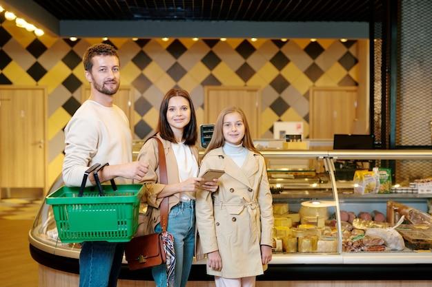 Zeitgenössische junge familie von vater, mutter und ihrer jugendlichen tochter in freizeitkleidung, die im supermarkt steht