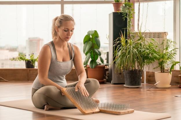 Zeitgenössische junge fit-frau in aktivkleidung, die auf der matte sitzt, während sie yoga-übung mit massagekissen für sohlen und handflächen übt