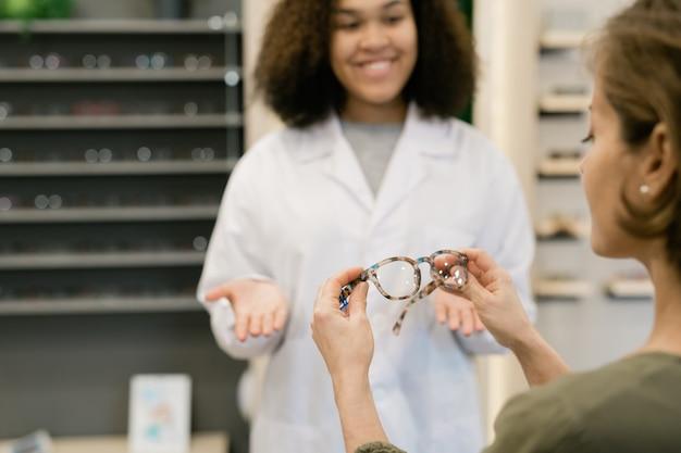 Zeitgenössische junge frau, die stilvolle brillen hält, während mischrassenkliniker im weißmantel sie berät