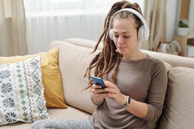 Zeitgenössische junge frau mit dreadlocks, die musik in kopfhörern hören und im smartphone auf couch scrollen