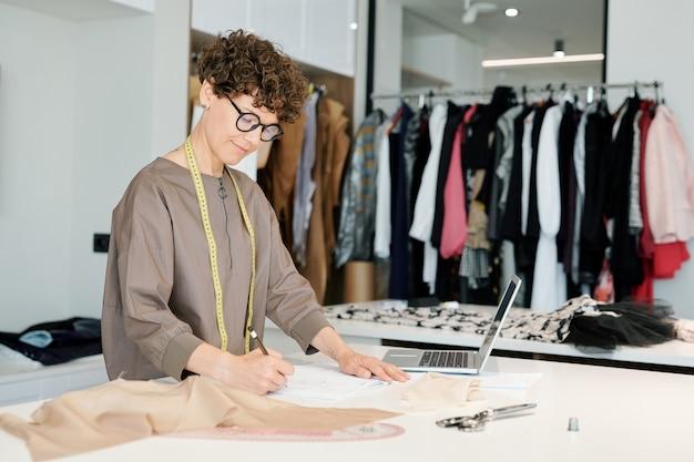 Zeitgenössische junge freizeitdesignerin mit maßband auf ihrem hals, der skizze des kleidungsstücks zeichnet