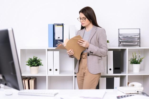 Zeitgenössische junge geschäftsfrau oder buchhalterin, die durch finanzpapiere schaut, während sie durch regale im büro steht