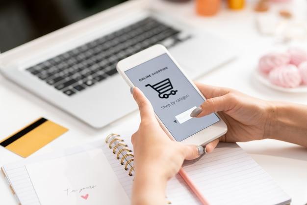 Zeitgenössische junge kundin mit smartphone, die waren im online-shop sucht, während sie bestellung macht