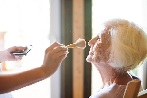 Zeitgenössische kosmetikerin mit puderpinsel, die über make-up der älteren dame vor dem fotoshooting arbeitet