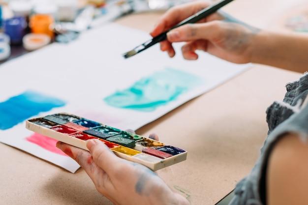 Zeitgenössische kunst. beschnittene aufnahme der jungen malerin, die abstrakte kunstwerke mit aquarell schafft.