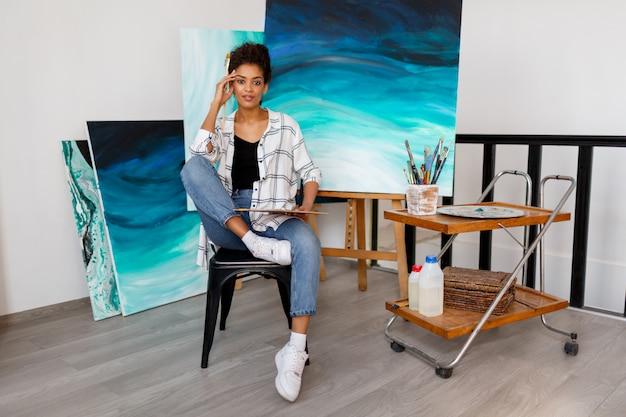 Zeitgenössische kunst. talent und kreativität. inspirierte junge schwarze dame, die an ihrem abstrakten kunstwerk des ozeans arbeitet.