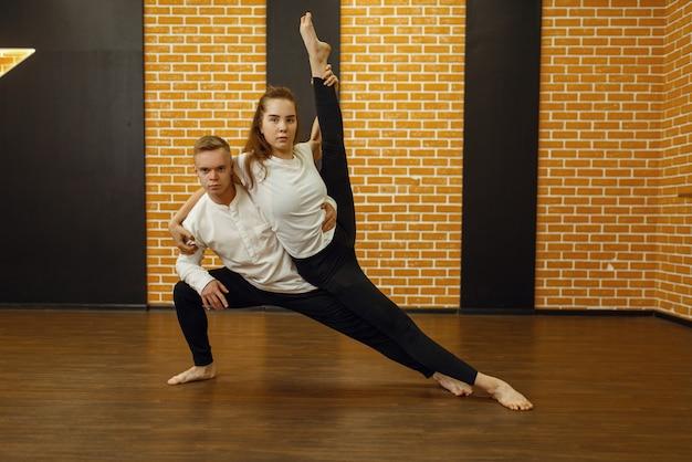 Zeitgenössische tanzdarsteller, paar posiert im studio. männliche und weibliche tänzer beim training im unterricht, moderner tanz, dehnübungen