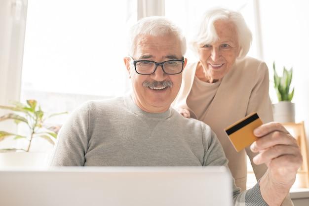 Zeitgenössischer älterer mann mit plastikkarte, die vor laptop beim online-einkauf und beim bezahlen für bestellungen sitzt