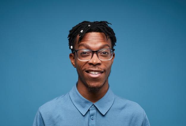 Zeitgenössischer afrikanischer mann, der auf blau lächelt