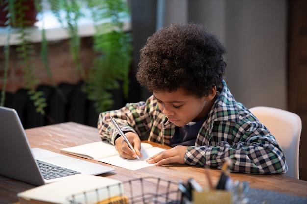 Zeitgenössischer afrikanischer schuljunge in freizeitkleidung, der notizen im schreibheft macht, während er am tisch vor dem laptop sitzt und hausaufgaben macht