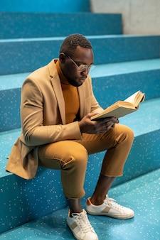 Zeitgenössischer afrikanischer student mit offenem buchlesen auf blauer treppe