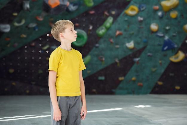 Zeitgenössischer aktiver schüler im gelben t-shirt und in der grauen hose, die im sportzentrum stehen