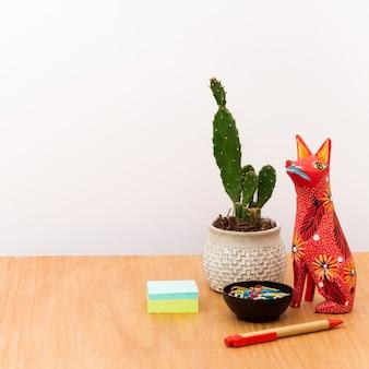 Zeitgenössischer arbeitsplatz mit kaktus im topf und in der statue