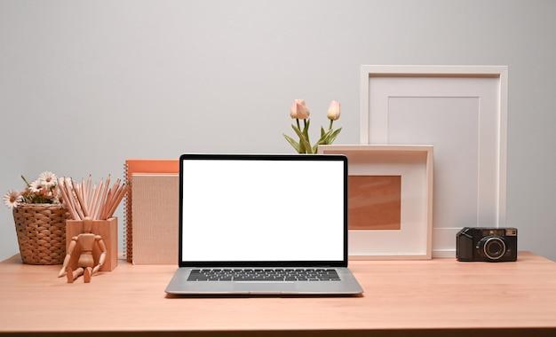 Zeitgenössischer arbeitsplatz mit laptop-computer-bilderrahmen und bleistifthalter.