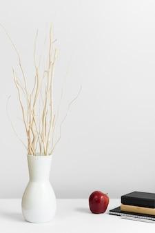 Zeitgenössischer arbeitsplatz mit vase und apfel auf schreibtisch