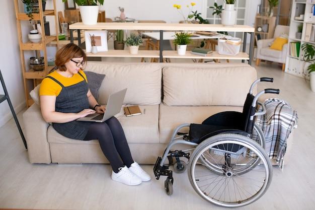 Zeitgenössischer behinderter student mit laptop, der auf couch in häuslicher umgebung sitzt und im netz während der suche nach online-kurs surft