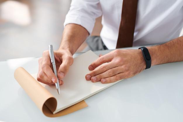 Zeitgenössischer designer bereit, notizen zu machen oder hand in hand mit stift über leere seite des notizblocks zu skizzieren
