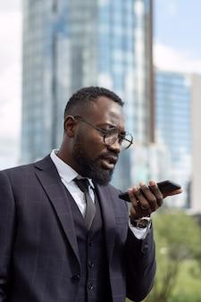 Zeitgenössischer geschäftsmann, der sprachnachrichten auf dem smartphone aufzeichnet
