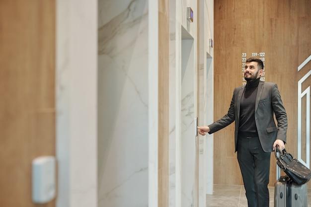 Zeitgenössischer geschäftsreisender im anzug, der knopf an der wand drückt, während er an einer der aufzugstüren im hotel steht
