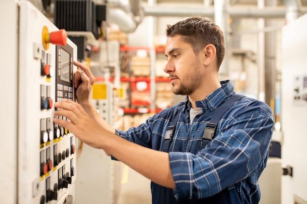 Zeitgenössischer ingenieur einer großen industrieanlage, der die einstellungen der maschinen vor der verarbeitung der chemischen rohsubstanz anpasst