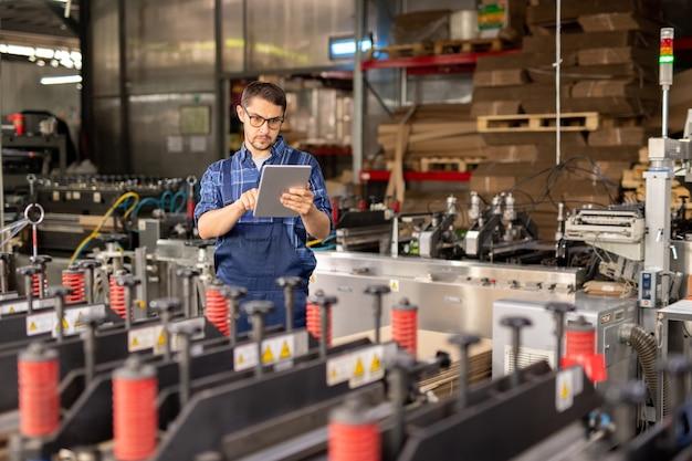 Zeitgenössischer ingenieur einer industrieanlage mit touchpad im stehen an einer großen industriemaschine in der werkstatt