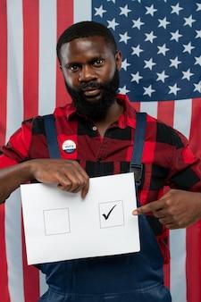 Zeitgenössischer junger afroamerikanischer handwerker, der auf tick in einem der quadrate auf stimmzettel zeigt, während er gegen us-flagge steht