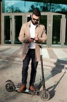 Zeitgenössischer junger eleganter geschäftsmann, der im smartphone während des stehens auf elektroroller im freien rollt oder schreibt