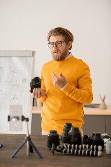 Zeitgenössischer junger professioneller fotograf, der eine fotokamera hält und seinem online-publikum im unterricht erklärt, wie es funktioniert