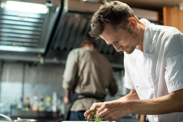 Zeitgenössischer junger professioneller männlicher koch, der sich über den küchentisch beugt, während er grünen dill oder petersilie zum dekorieren von gemüse oder fleisch wählt