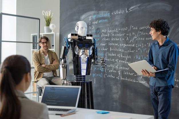 Zeitgenössischer junger student mit laptop, der durch tafel im klassenzimmer steht und präsentation des computerroboters macht
