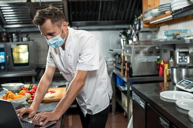 Zeitgenössischer koch in uniform und schutzmaske, der online-rezepte auf dem laptop-display durchsieht, während er am arbeitsplatz in der küche steht