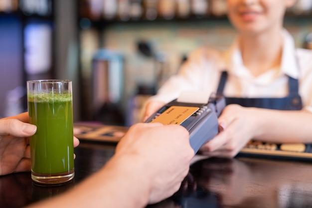 Zeitgenössischer kunde, der plastikkarte über bildschirm des zahlungsterminals hält, während für glas glasgemüsesmoothie im café bezahlt wird