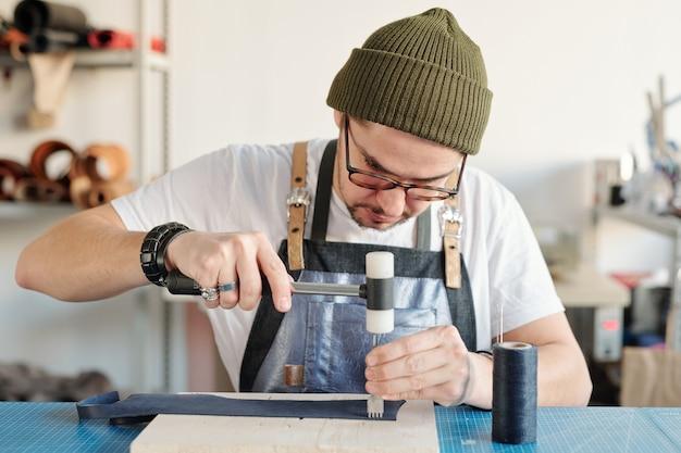 Zeitgenössischer lederarbeiter oder handwerksmeister, der handwerkzeuge verwendet, um ein stück schwarzes leder zu verarbeiten, das auf einem holzbrett liegt