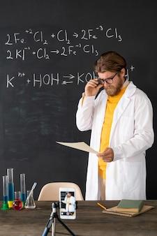 Zeitgenössischer lehrer im weißmantel, der aufzeichnung des chemieunterrichts für sein online-publikum auf smartphone-kamera gegen tafel macht