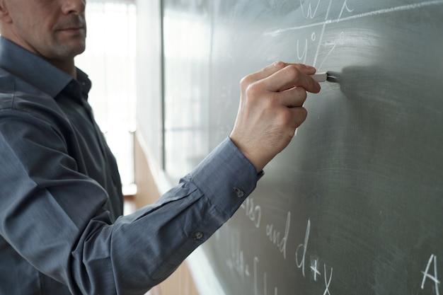 Zeitgenössischer lehrer mit kreide, der formel auf tafel schreibt