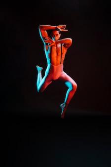 Zeitgenössischer männlicher balletttänzer, der im scheinwerferlicht durchführt