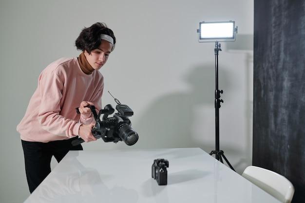 Zeitgenössischer männlicher vlogger mit videokamera, die neue fotoausrüstung auf schreibtisch im studio schießt
