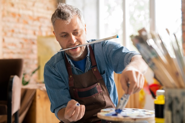 Zeitgenössischer maler in arbeitskleidung, der am tisch in der werkstatt sitzt, während er ölfarbe aus der tube drückt, bevor er farben auf palette mischt