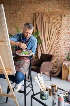 Zeitgenössischer maler in freizeitkleidung und schürze, die farben auf palette mischen, während sie vor staffelei im studio sitzen