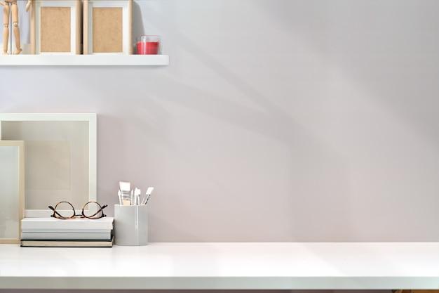 Zeitgenössischer minimaler arbeitsplatz mit weißem holztisch- und kopienraum