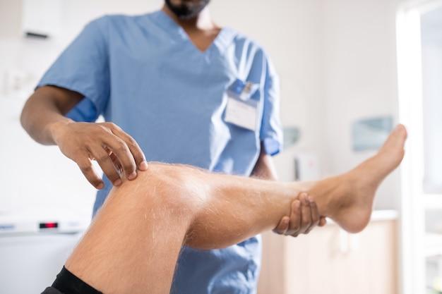 Zeitgenössischer mischlingsprofi in uniform, der das kranke knie seines patienten während der medizinischen untersuchung berührt