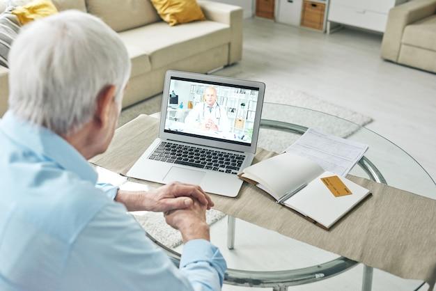 Zeitgenössischer rentner, der am tisch vor laptop sitzt und online-video mit rücksprache mit dem arzt zu hause sieht