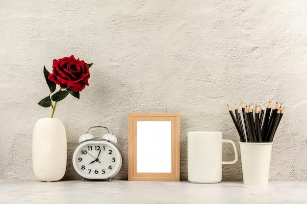 Zeitgenössischer schreibtisch an arbeitsplatz mit büroartikel und weißzementwand.