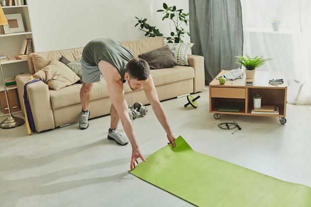 Zeitgenössischer sportler, der matte auf den boden legt, während er yoga-übungen in der häuslichen umgebung während der quarantänezeit macht